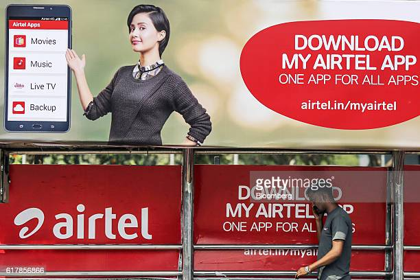 A pedestrian talks on a mobile phone while walking below a billboard advertisement for Bharti Airtel Ltd displayed above a bus stop in Mumbai India...