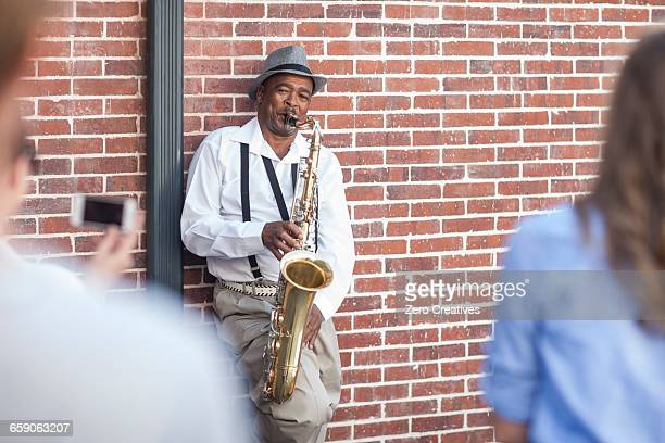 Pedestrian throwing money into street musicians music case, low section