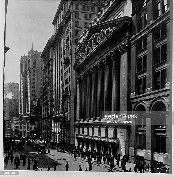 Pedestrian traffic rushes to either side of Broad Street below the New York Stock Exchange in the financial district ca 1915 New York City
