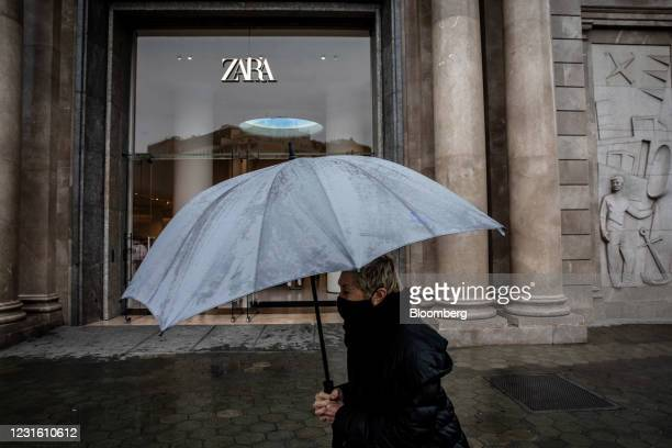 Pedestrian under an umbrella passes a Zara clothing store, operated by Inditex SA, in Barcelona, Spain, on Monday, March 8, 2021. Inditex will report...