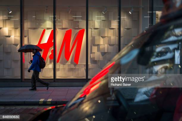 A pedestrian under an umbrella walks past the HM logo on 28th February 2017 in the City of London England