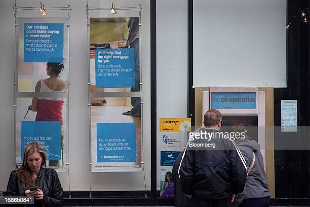A pedestrian uses a mobile handset as customers use an automated teller machine at a CoOperative Bank Plc branch in London UK on Monday May 13 2013...