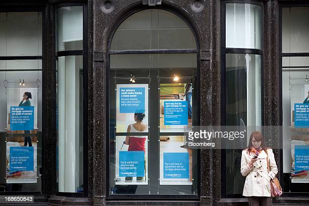 A pedestrian uses a mobile handset as she stands outside a CoOperative Bank Plc branch in London UK on Monday May 13 2013 CoOperative Bank Plc Chief...