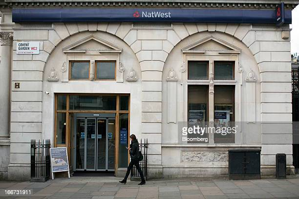 A pedestrian uses a mobile handset as she walks past a NatWest bank branch part of the Royal Bank of Scotland Group Plc in London UK on Tuesday April...