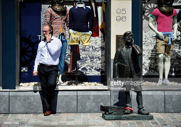 A pedestrian uses a mobile handset near 'The Echo Boy' sculpture by artist Barry Moloney in Cork Ireland on Tuesday June 4 2013 Speaking to lawmakers...