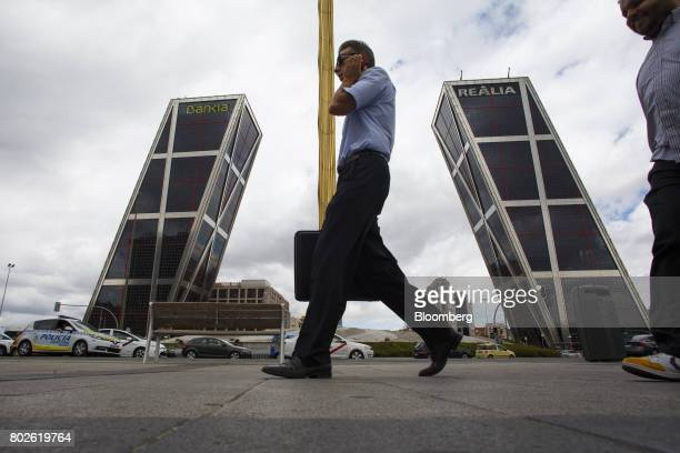 A pedestrian uses a smartphone as he passes the headquarters of Bankia SA at the Kio towers in Madrid on Wednesday June 28 2017 Bankia SAagreed to...