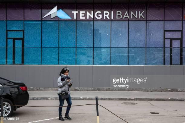 Pedestrian uses a smartphone while walking past a Tengri Bank JSC branch in Astana, Kazakhstan, on Friday, April 13, 2018. Kazakhstan's gross...