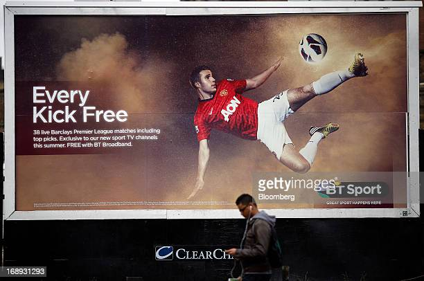 A pedestrian uses an personal electronic device as he passes a billboard advertisement for BT Group Plc's new sports television service BT Sport in...