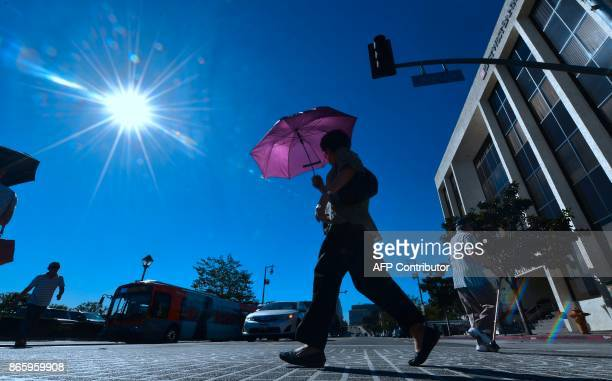 Pedestrian uses an umbrella on a hot sunny morning in Los Angeles October 24, 2017 amid a late season heatwave hitting southern California. Record...