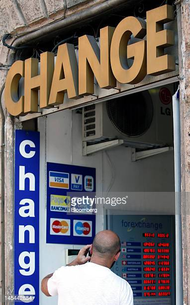 A pedestrian uses his mobile phone as he looks at foreign exchange rates displayed on a board inside a currency exchange store in Rome Italy on...