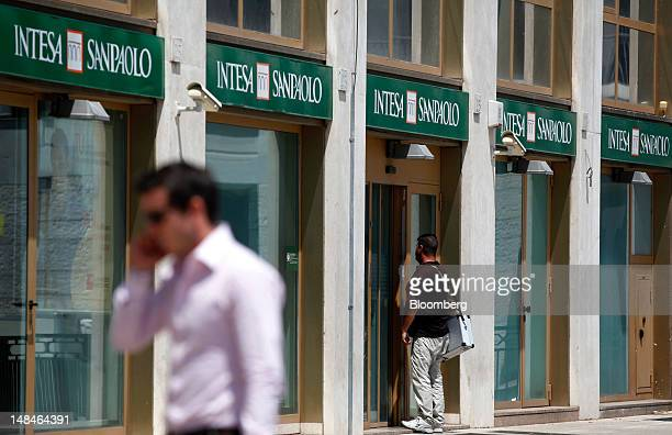 Pedestrian uses his mobile phone as he passes an Intesa Sanpaolo SpA bank branch in Rome, Italy, on Tuesday, July 17, 2012. UniCredit SpA and Intesa...