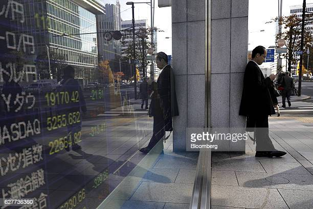 A pedestrian uses his mobile phone in front of an electronic stock board at a securities firm in Tokyo Japan on Monday Dec 5 2016 Japanese shares...