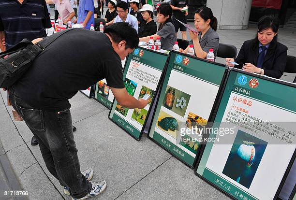 A pedestrian uses his mobile phone to take photos of antidrug posters on display ahead of the UN's antidrug day in Beijing on June 26 2008 China has...