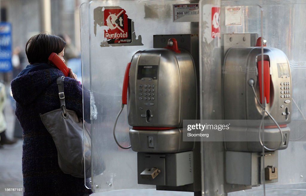 A pedestrian uses the handset of a payphone operated by Telecom Italia SpA, in Milan, Italy, on Tuesday, Nov. 20, 2012. Telecom Italia SpA said it is still reviewing the possible spinoff of its fixed-line network and the company's board will discuss the outcome of its analysis on Dec. 6. Photographer: Alessia Pierdomenico/Bloomberg via Getty Images