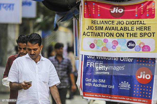 A pedestrian using a mobile phone walks past banners for Reliance Jio the mobile network of Reliance Industries Ltd and Bharti Airtel Ltd outside a...