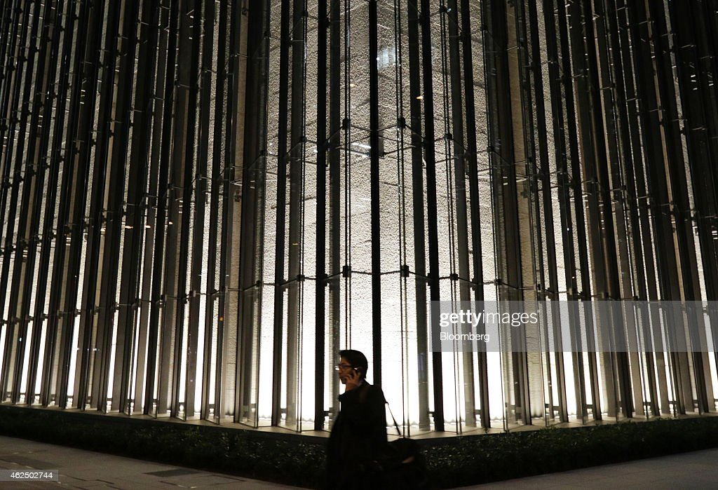 A pedestrian using a mobile phone walks past the Mizuho Financial Group Inc. headquarters in Tokyo, Japan, on Thursday, Jan. 29, 2015. Mizuho Financial Group, Japan's third largest bank, is scheduled to report third-quarter earnings on Jan. 30. Photographer: Tomohiro Ohsumi/Bloomberg via Getty Images