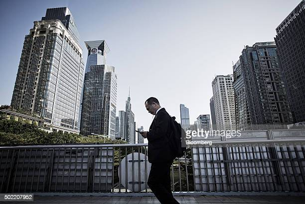 A pedestrian using a smartphone walks along a pedestrian bridge as commercial buildings stand in the background in Shenzhen China on Wednesday Dec 16...
