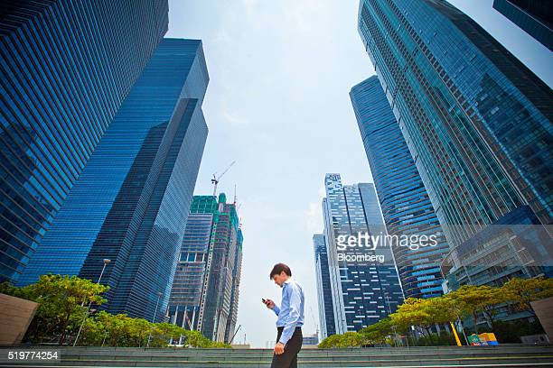 A pedestrian using a smartphone walks in front of commercial buildings in the central business district of Singapore on Friday April 8 2016 Singapore...
