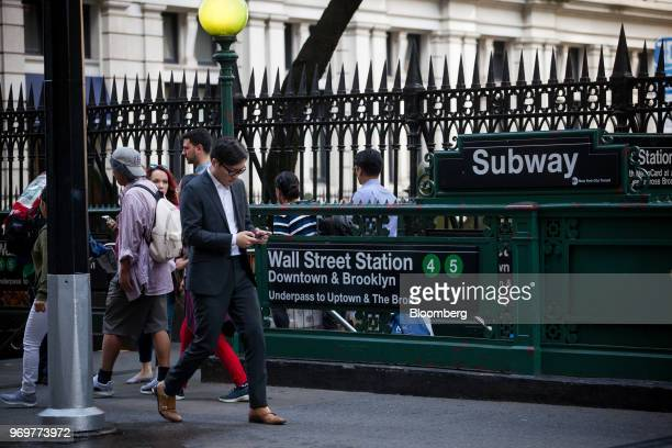Pedestrian views a mobile device while walking past the Wall Street subway station near the New York Stock Exchange in New York, U.S., on Friday,...
