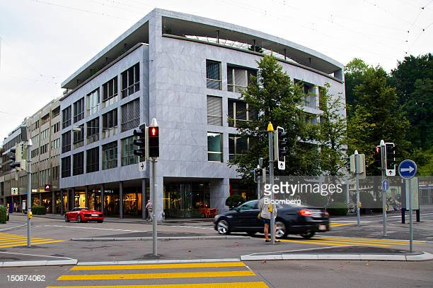 Pedestrian waits at an intersection in front of building that houses the headquarters of Xstrata Plc in Zug, Switzerland, on Friday, Aug. 24, 2012....