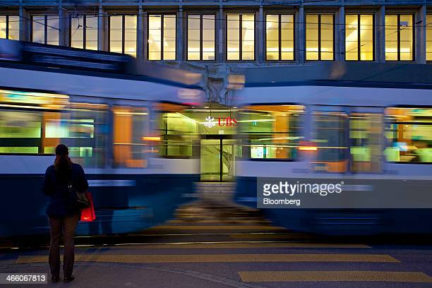 A pedestrian waits for a tram to pass before crossing a road near UBS AG's headquarters in Zurich Switzerland on Thursday Jan 30 2014 UBS's board...