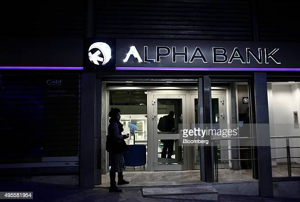 A pedestrian waits outside the entrance to an Alpha Bank AE bank branch in Athens Greece on Tuesday Nov 3 2015 Greece's four biggest banks may need...