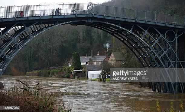 Pedestrian walk across a bridge over the swollen River Severn at Ironbridge near Telford in Shropshire on December 24 2012 Heavy flooding across...