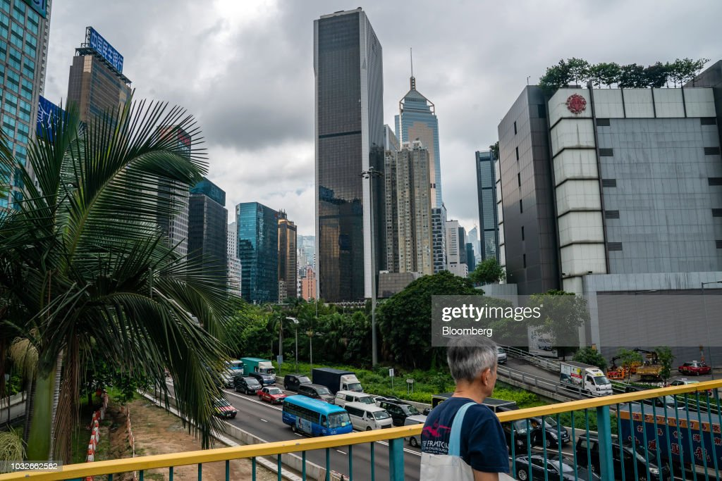 A pedestrian walk across a footbridge as the Sun Hung Kai Centre building, which houses the Sun Hung Kai Properties Ltd. headquarters, center, stands in Hong Kong, China, on Thursday, Sept. 13, 2018. Sun Hung Kai, Hong Kong's biggest developer, reported a 17 percent rise in annual earnings as the city's residential market maintained its upward momentum. Photographer: Anthony Kwan/Bloomberg via Getty Images