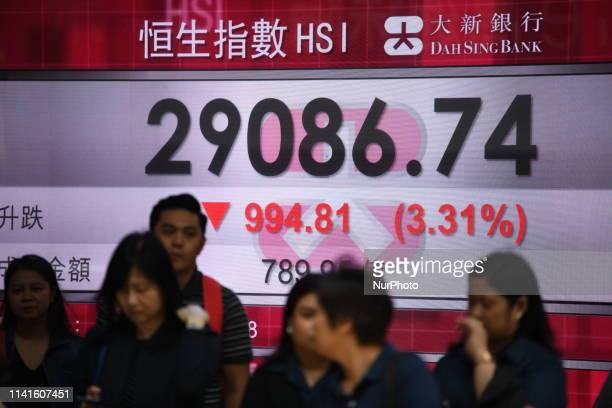 Pedestrian walk pass a electronic display board with displaying the Hang Seng Index In Hong Kong China 6 May 2019 The Hang Seng Index plunged over...