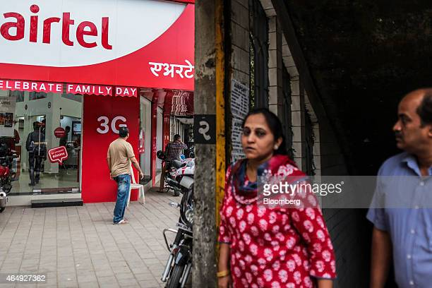Pedestrian walk past a Bharti Airtel Ltd store in Mumbai India on Saturday Feb 28 2015 The government auction of telecom wireless spectrum starting...