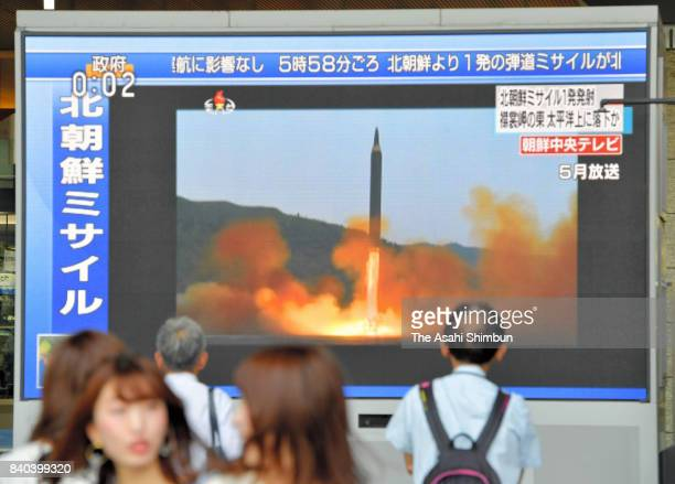 Pedestrian walk past a screen reporting the news of North Korea's missile launch in front of JR Osaka Station on August 29 2017 in Osaka Japan The...