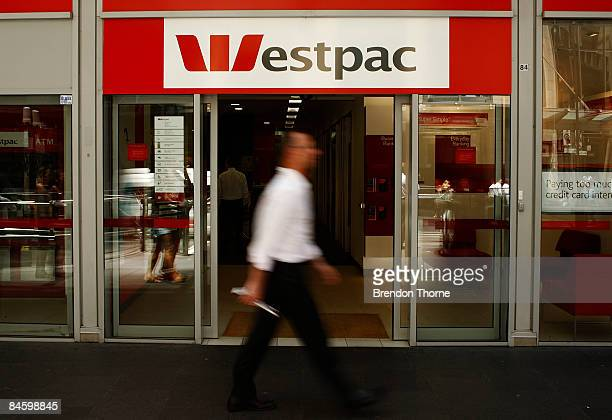 Pedestrian walk past a Westpac branch in Sydney as economists wait to see if The Reserve Bank of Australia cut official interest rates today at the...
