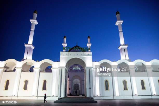 A pedestrian walk pasts the NurAstana Mosque at night in Astana Kazakhstan on Saturday April 14 2018 Kazakhstan's gross domestic product for the...
