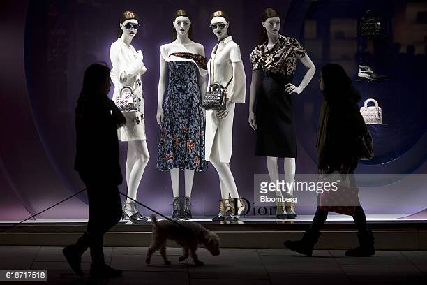 A pedestrian walking a dog passes a display of luxury fashions at a Christian Dior SA store on New Bond Street in London UK on Thursday Oct 27 2016...
