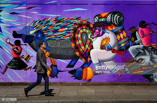 Pedestrian walking past graffiti wall on construction hoarding in Great Eastern Street East London