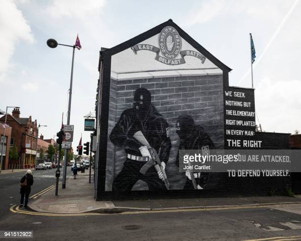 pedestrian walking past mural in belfast, northern ireland - irish republican army stock photos and pictures