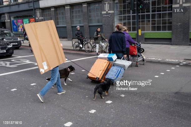 Pedestrian walking two dogs carries a wrapped square item across the road in Hoxton, on 24th February 2021, in London, England.