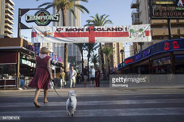 A pedestrian walks a dog across a road crossing towards the entrance to a bar lined street decorated with a banner reading C'mon England in Benidorm...