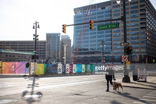 A pedestrian walks a dog in front of the Hudson's Site development as construction is halted in Detroit Michigan US on Saturday April 4 2020 Metro...