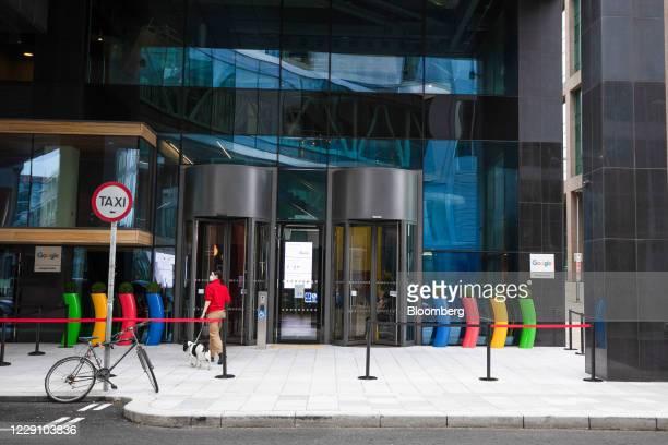 Pedestrian walks a dog near the Google Inc. European headquarters in Dublin, Ireland, on Thursday, Oct. 15, 2020. Office vacancy rate rose from 6.65%...