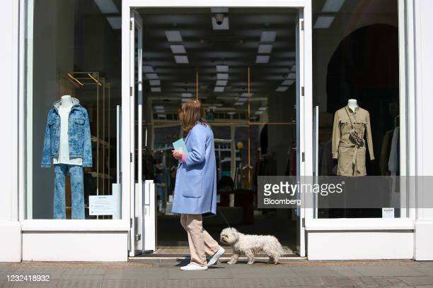 Pedestrian walks a dog past a clothing store in Chelsea, London, U.K., on Tuesday, April 20, 2021. The U.K. Economy is building momentum,...