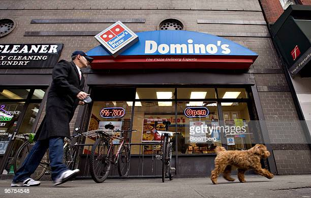 A pedestrian walks a dog past a Domino's Pizza franchise on 89th Street in New York US on Wednesday Jan 13 2010 Domino's Pizza Inc the secondlargest...
