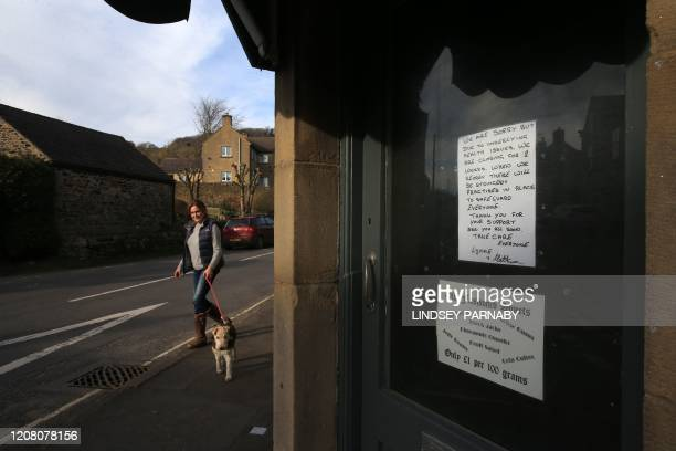 A pedestrian walks a dog past a shop that is closed due to the coronavirus outbreak in the village of Eyam in Derbyshire northern England on March 23...