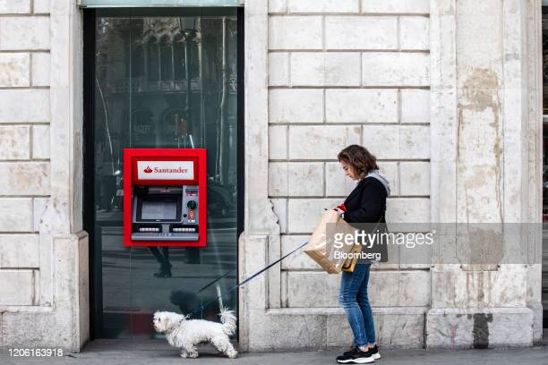 A pedestrian walks a dog past an automated teller machine outside a Banco Santander SA bank branch in Barcelona Spain on Friday March 6 2020 Spanish...