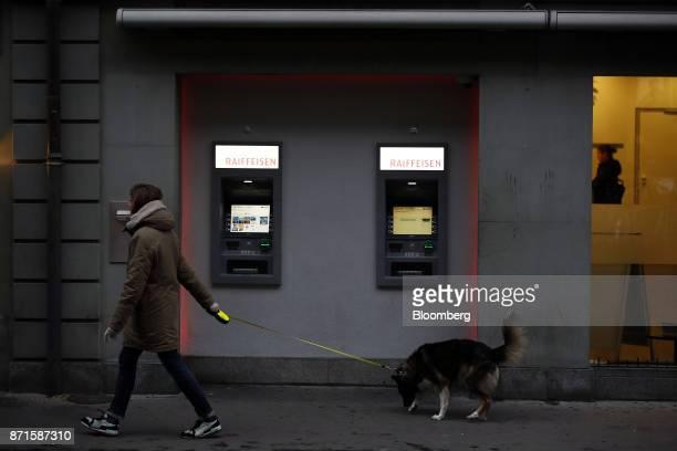 A pedestrian walks a dog past automated teller machines outside a Raiffeisen Schweiz Genossenschaft bank branch in Bern Switzerland on Tuesday Nov 7...