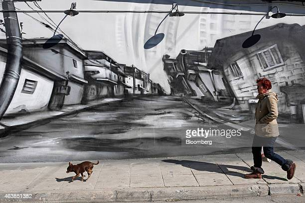 A pedestrian walks a small dog along a street past a graffiti street view in Athens Greece on Thursday Feb 19 2015 Germany rebuffed Greece's request...