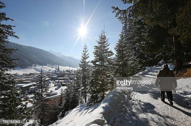 A pedestrian walks along a mountain path with views over snow covered buildings in the town of Davos Switzerland on Friday Jan 18 2013 Next week the...