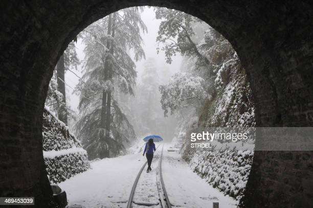 Pedestrian walks along a narrow-gauge railroad track during heavy snowfall in the northern hill town of Shimla on February 15, 2014. Heavy snow in...
