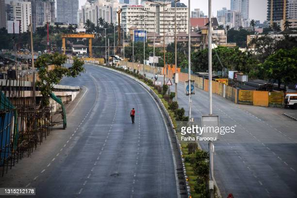 Pedestrian walks along a near-deserted street during a lockdown imposed to try and contain the spread of Covid-19 on April 29, 2021 in Mumbai, India....