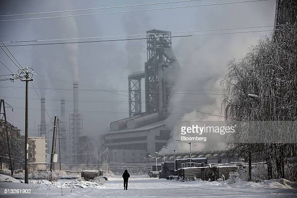 A pedestrian walks along a road as water vapor and smoke rise from a Tonghua Iron Steel Group Co plant in the Erdaojiang district in Tonghua Jilin...